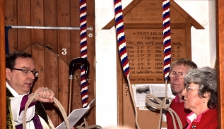 The Bishop hands a bell rope to Janeve Bainbridge (Tower Captain). Phil Simpson (Steeple Keeper) looks on.
